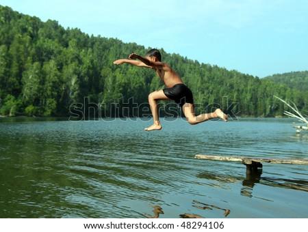 summer vacations - boy jumping in lake - stock photo