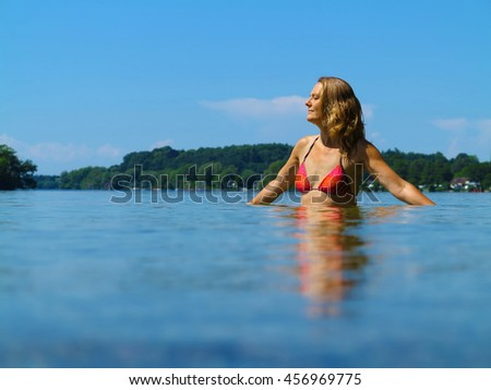 summer vacations image with adult midlife woman relaxing in a beautiful lake - stock photo