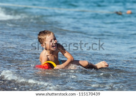 Summer vacations - little smiling child boy playing on sea sand beach - stock photo