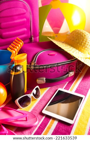 Summer vacations packing with colorful accessories and digital tablet. - stock photo