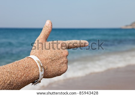 Summer vacations - woman hand index finger pointing direction to sea sand beach