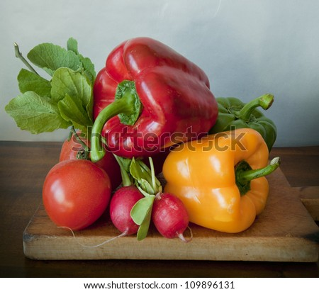 Summer vegetables: tomatoes, yellow red, green peppers and radishes on a wooden block - stock photo