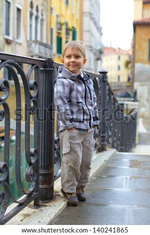 Summer venetian view and tourist boy. Venice, Italy. - stock photo