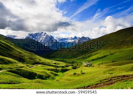 Summer view of Dolomites valley, under blue sky with clouds. - stock photo
