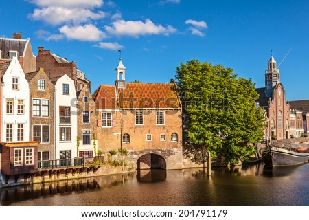 Summer view of medieval houses alongside a canal in Delfshaven, The Netherlands - stock photo