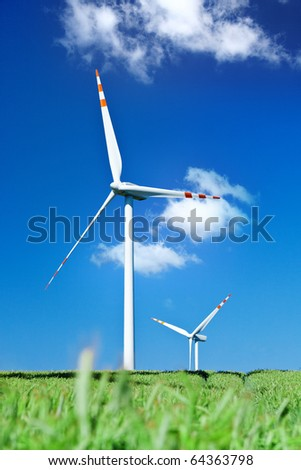 summer view of two wind turbines from grass leve - stock photo