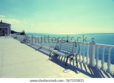 Summer view with classic white balustrade, benches and empty terrace overlooking the sea, sunlight. Vintage toned image - stock photo