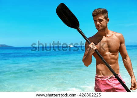 Summer Water Sport. Handsome Athletic Man With Sexy Body In Swimwear Holding Canoe Kayak Paddle. Beautiful Fitness Male Model Having Fun At Tropical Sea Beach. Recreational Leisure Sporting Activity - stock photo