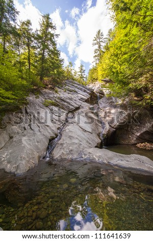 Summer waterfall flowing into a peaceful freshwater stream with stones. - stock photo