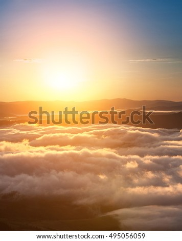 Summer weather phenomenon. Seasonal landscape with morning fog in valley. Clouds drenched valley below the level of the mountains. Sunrise over creeping clouds.