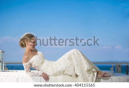 Summer wedding. Beautiful bride on the sea. Romantic beautiful bride in white dress posing on terrace with sea in background - stock photo