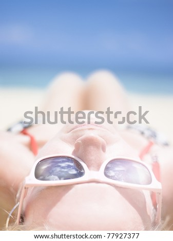 Summer Woman Laying On The Beach Wearing Summer Sunglasses With The Sun Beaming Down