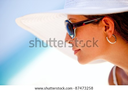 Summer woman looking at the horizon, wearing hat and sunglasses - stock photo