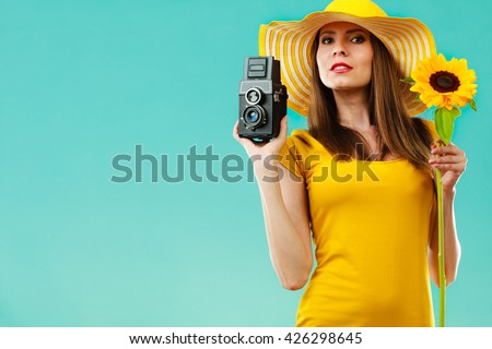 summer woman wearing yellow dress and hat with sunflower and old vintage camera in hand on vivid blue background