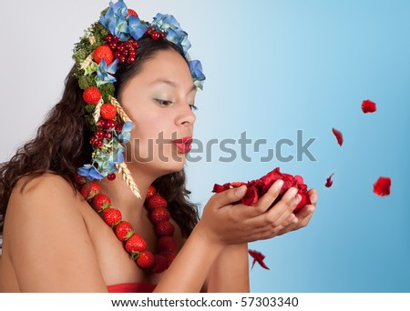 Summer woman with strawberries, fruit and flowers in her hair blowing rose petals