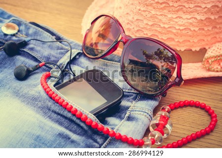 Summer women's accessories: red sunglasses, beads, denim shorts, mobile phone, headphones, a sun hat. Toned image  - stock photo