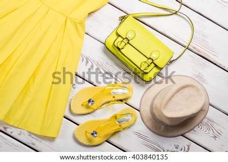 Summer women's accessories. Yellow dress, sandals, colorful handbag and straw hat. - stock photo