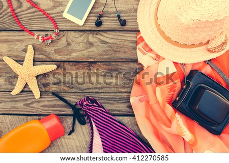 Summer women's beach accessories for your sea holiday on the old wooden background. Toned image.  - stock photo
