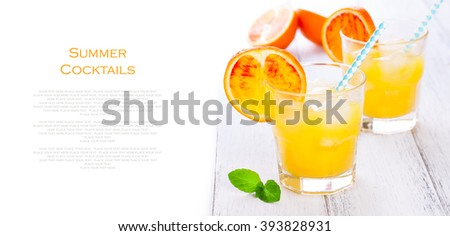 Summer yellow orange lemonade with ice and peaces of blood oranges and straw on a wooden table on a white background with place for text, copy space, horizontal, closeup - stock photo
