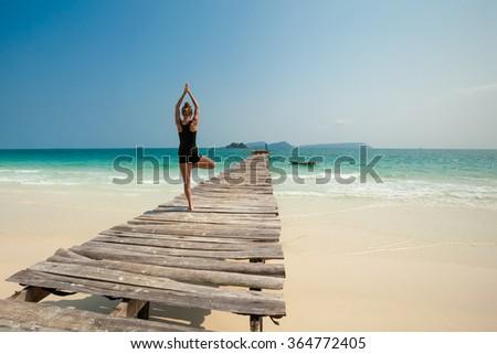 Summer yoga session on a beach - tropical Koh Rong island, Cambodia. Vriksha-asana - tree pose. - stock photo