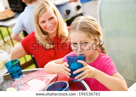 Summer: Young Girl Drinking From Glass Of Water During Dinner - stock photo
