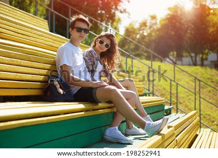 Summer young modern stylish couple in sunglasses rest in the city, hipsters teenagers in urban style, youth, fashion - concept - stock photo