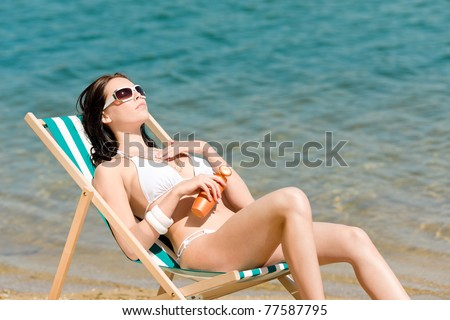 Summer young woman sunbathing in bikini on beach suncream