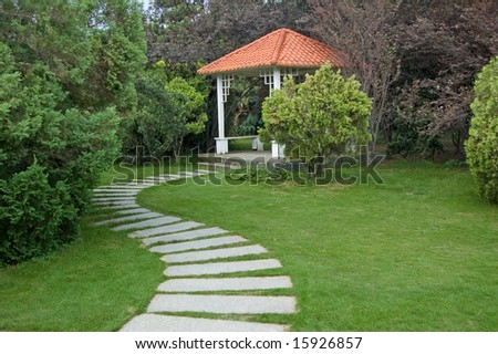 Summerhouse and curving walkway in the garden - stock photo