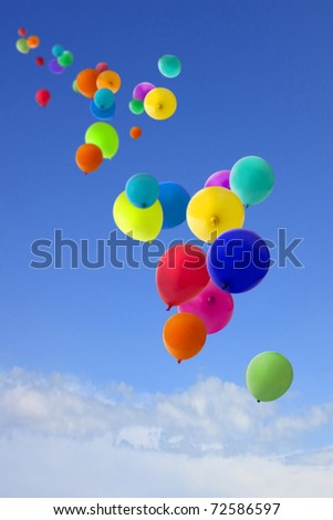 summers day with a host of coloured balloons floating into the blue sky - stock photo