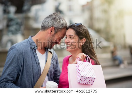 Summertime. A cheerful tourist couple visiting a city during their vacation, the grey haired man holds a mug of coffee and the brunette woman has shopping bags on her shoulder. Shot with flare