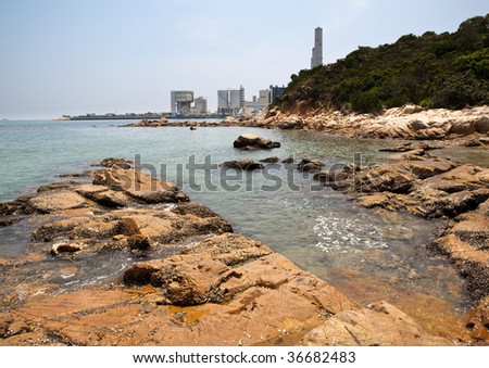 Summertime beach on Llama Island, Hong Kong with power plant background in the South China Sea