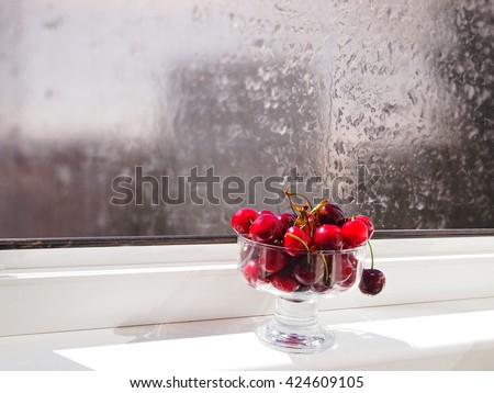 Summertime dream. Vase with a sweet cherry on a windowsill, raindrops on glass. - stock photo