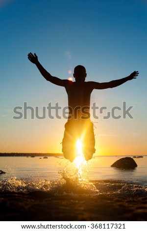 Summertime fun in the sea for joy. Jumping man silhouette on spectacular sunset background. Multicolored vibrant outdoors vertical image. - stock photo