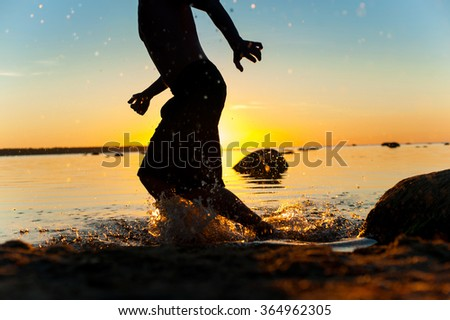 Summertime fun on the beach for joy. Running man silhouette on sunset background. Multicolored vibrant outdoors horizontal image. - stock photo