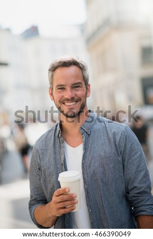 Summertime. Handsome man walking on the streets, he has a take away mug of coffee at hand