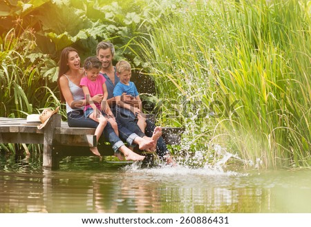 summertime, portrait of an happy family sitting on the edge of a wooden pontoon, feet in the river and making splashes - stock photo