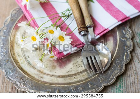 Summertime Table Setting with daisy flowers, napkin and silverware on wooden table - stock photo