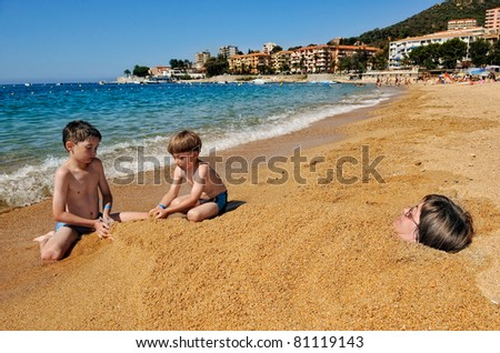 summertime - two boys playing on the beach, woman laying buried in the sand - stock photo