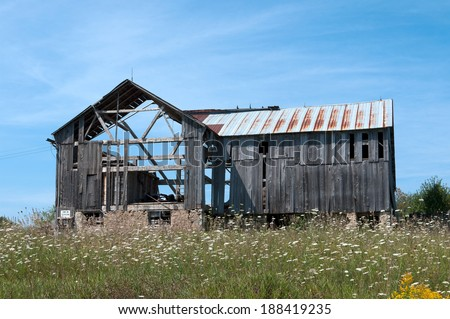 Summertime view of an old abandoned wood barn that is falling down. - stock photo