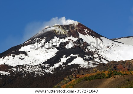 Summit craters of volcano etna with colorful autumn in the forest in the fall season - stock photo