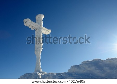 Summit Cross heavily freezed with snow and ice before a beatiful cloudless blue sky - stock photo