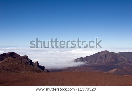 Summit of Haleakala, Maui crater overlooking the white clouds and blue sky - stock photo