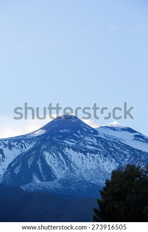 Summit of Mount Etna, active volcano in Sicily, Italy, spewing ash and gasses from its two erupting craters, photographed from the foothills.  Travel destination and forces of nature concept.  - stock photo