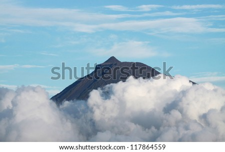 Summit of Volcano Mount Pico over clouds at Pico island (Azores) - stock photo