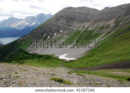 Summit view of mountain slopes, lake and meadows on the top of mountain indefatigable, kananaskis country, alberta, canada - stock photo