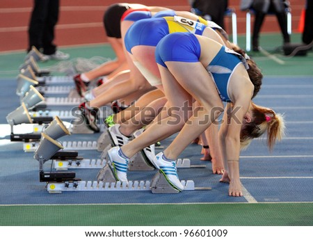 SUMY, UKRAINE - FEB.17: Unidentified girls on the start of the 60 meters dash during the Ukrainian Track and Field Championships on February 17, 2012 in Sumy, Ukraine. - stock photo