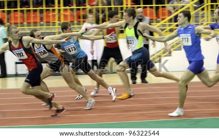 SUMY, UKRAINE - FEB 18: Unidentified men at the relay race on Ukrainian Track & Field Championships on February 18, 2012 in Sumy, Ukraine. - stock photo