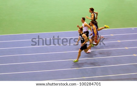 SUMY,UKRAINE -FEB.16: Unidentified men compete in the 60 meters dash during the Ukrainian Track and Field Championships on February 16, 2012 in Sumy, Ukraine. - stock photo