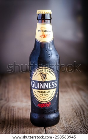 SUMY, UKRAINE - OCTOBER 26, 2014: A bottle of Guinness beer on a wooden background. Guinness is one of the most successful beer brands worldwide. - stock photo
