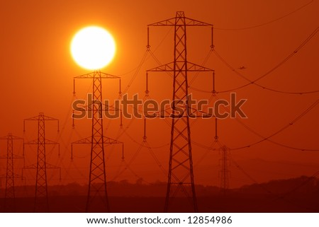 Sun above a row of electricity pylons - stock photo